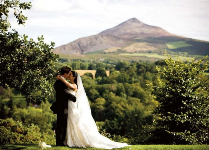 A happy Bride & Groom pictured on the grounds of Powerscourt Hotel Resort and Spa with Sugar Loaf Mountain in the background